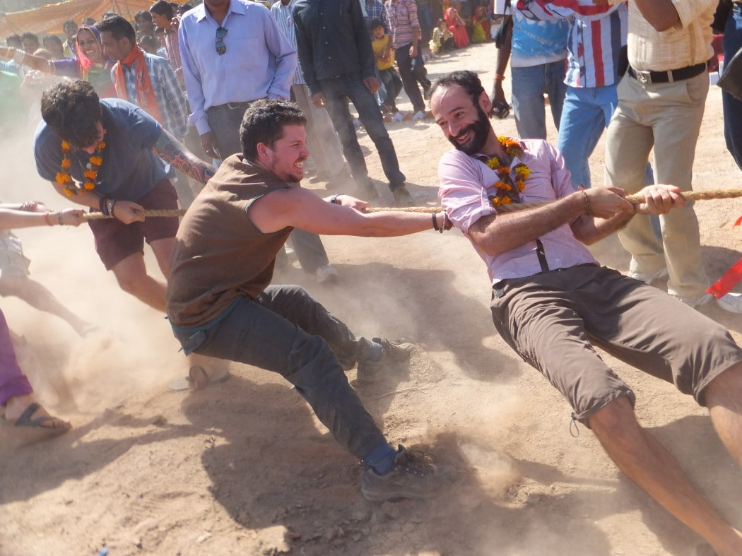 Several companions playing tug of war after becoming travel buddies in India