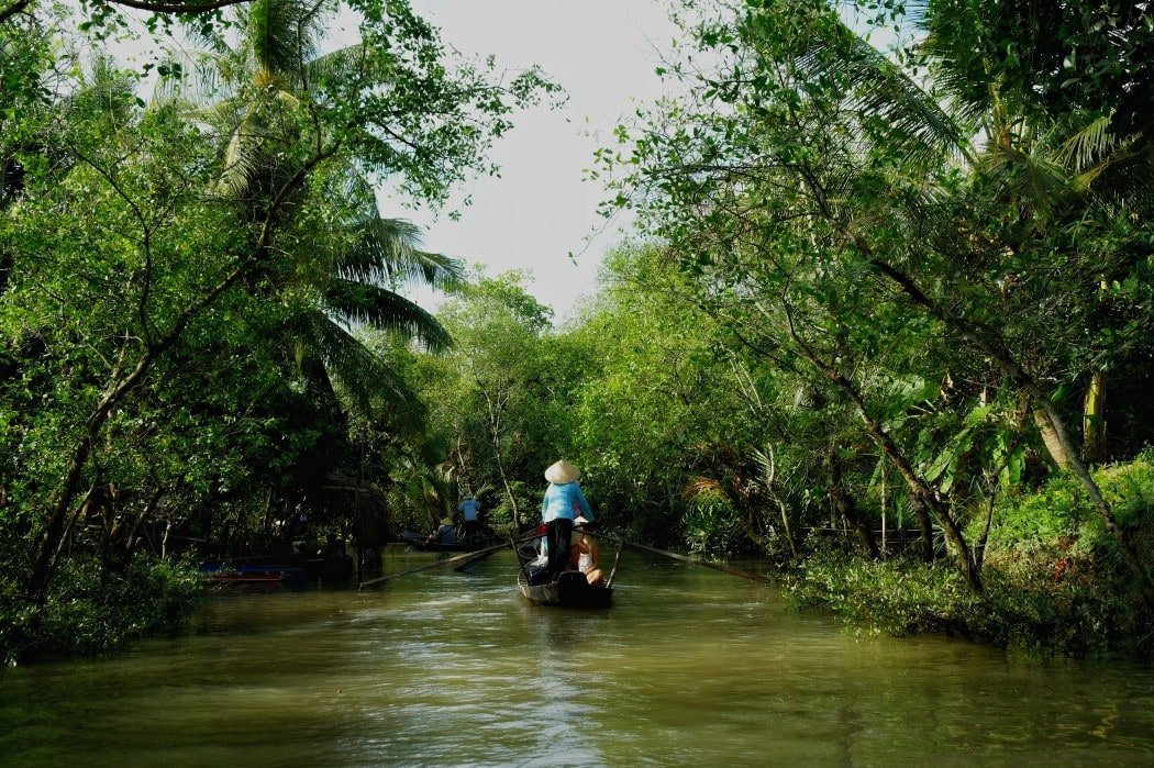Tourists take a boat ride down the Mekong Delta while visiting Vietnam
