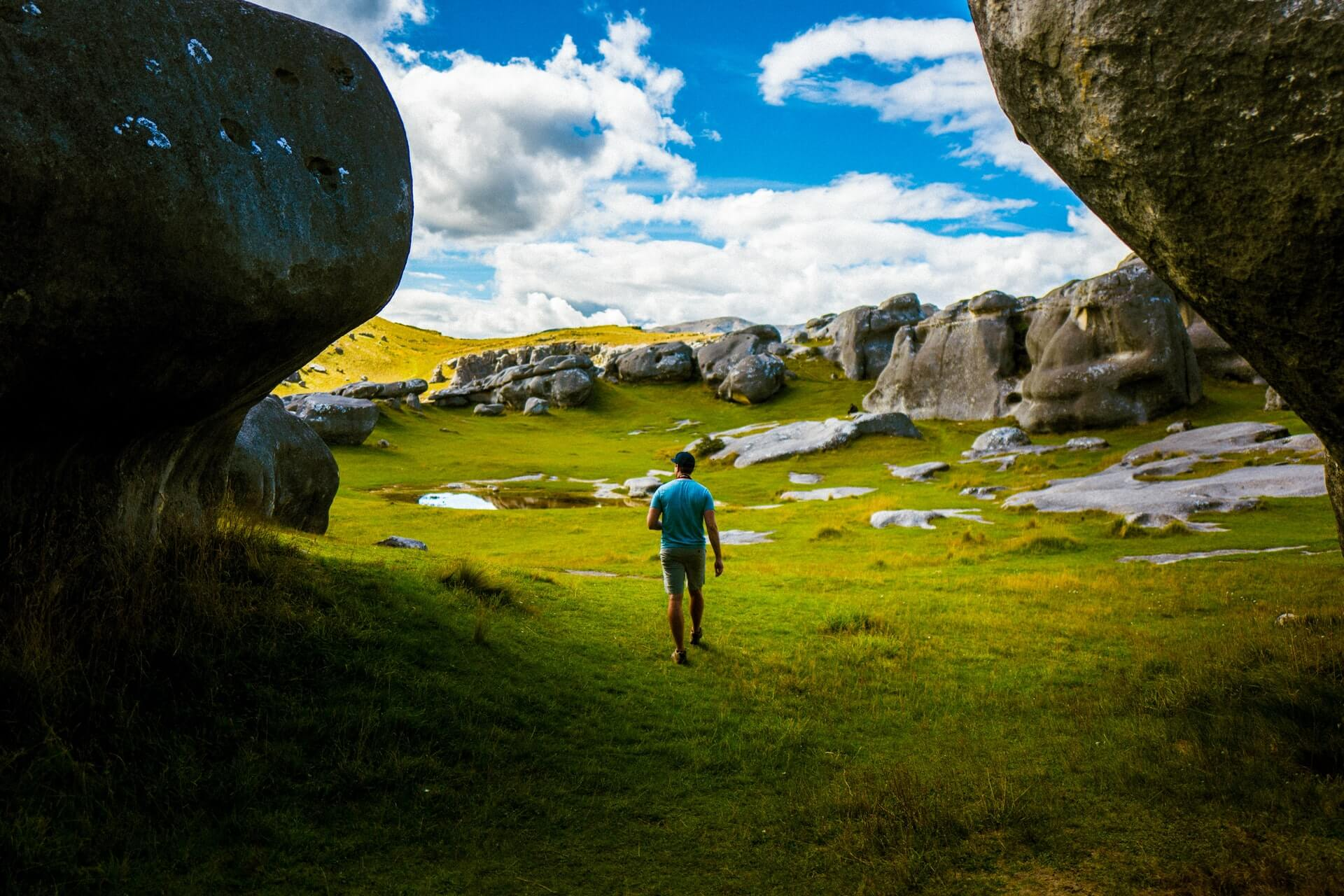 Backpacker travelling through South Island goes hiking at Castle Hill near Arthur's Pass