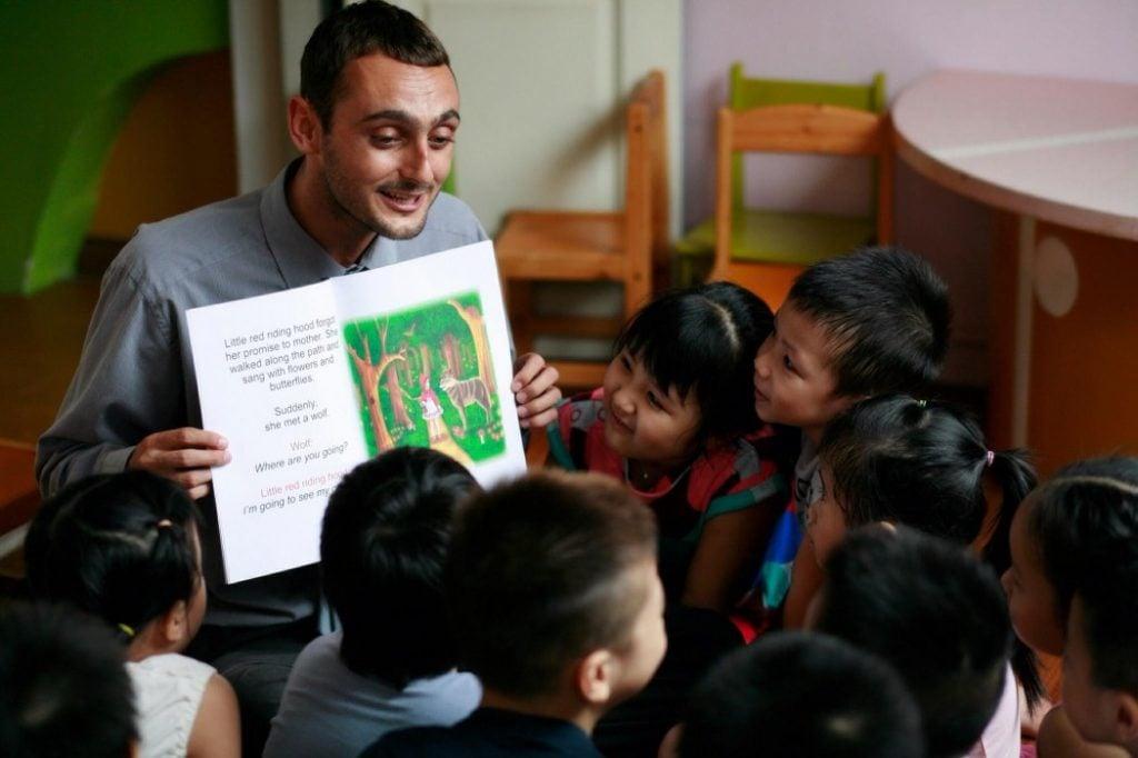 A man working in Vietnam teaching English to children
