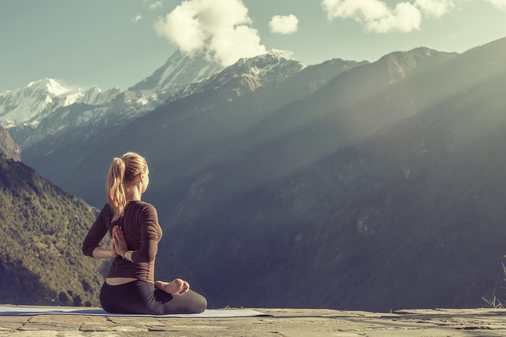 A working traveller doing yoga in the mountains