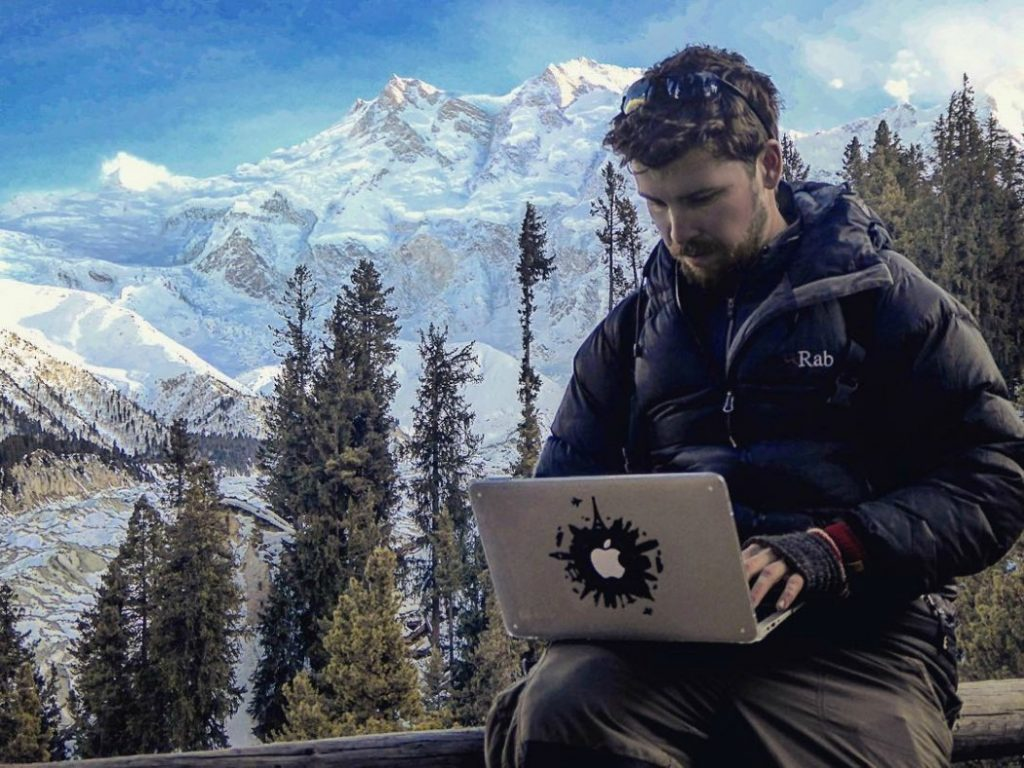 Will Hatton working on his laptop in Pakistan with an amazing view