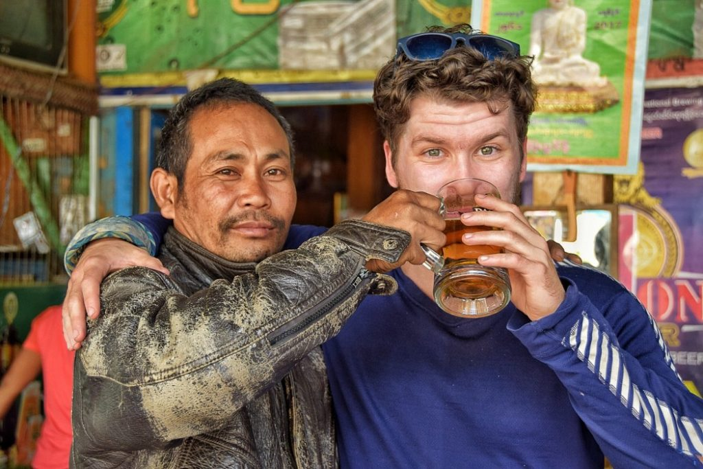 Will Hatton - The Broke Backpacker - drinking with a local man while trekking in Myanmar