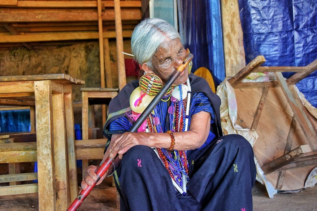 A local Myanmar woman in Chin State playing a nose flute