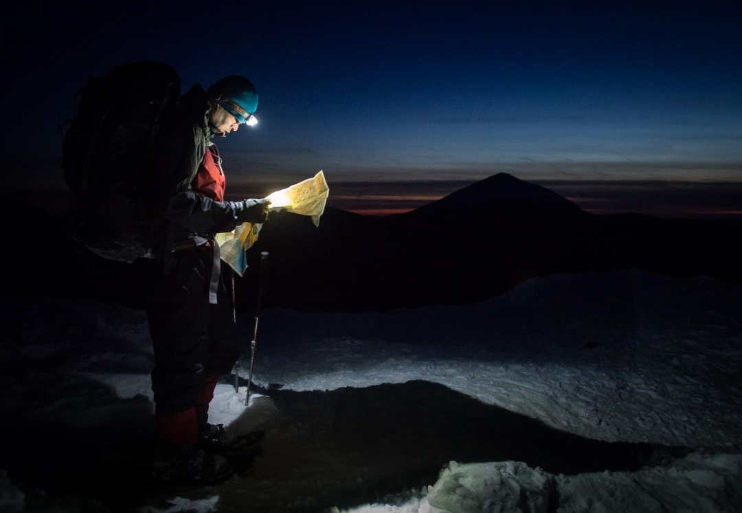 Man hiking with a headlamp - a backpacking essential