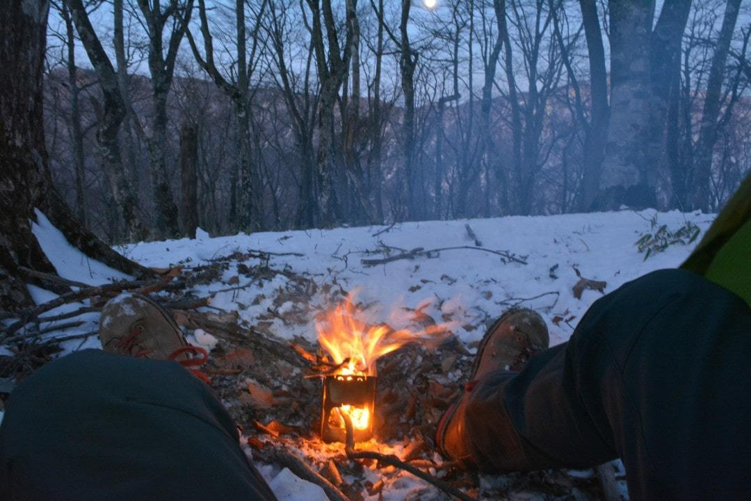 Warming up by your stove is a camping hack in winter