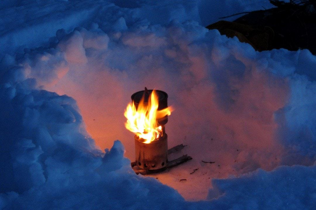 a top rated backpacking stove cooking in the snow