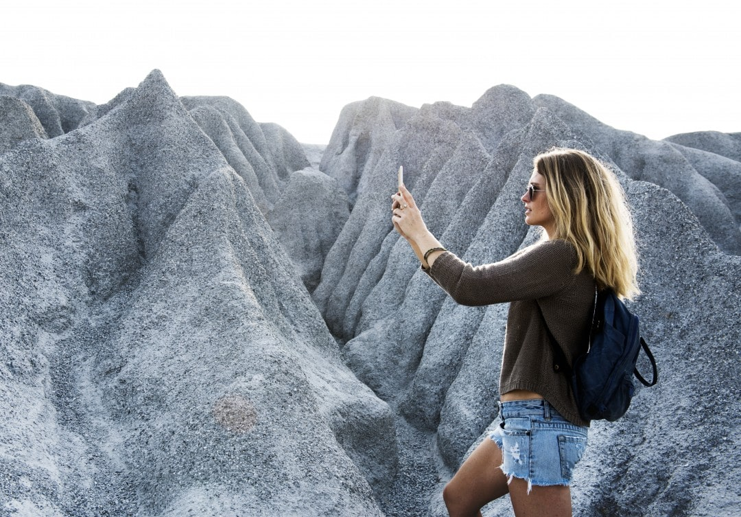 Girl taking picture of landscape- importance of photo backup
