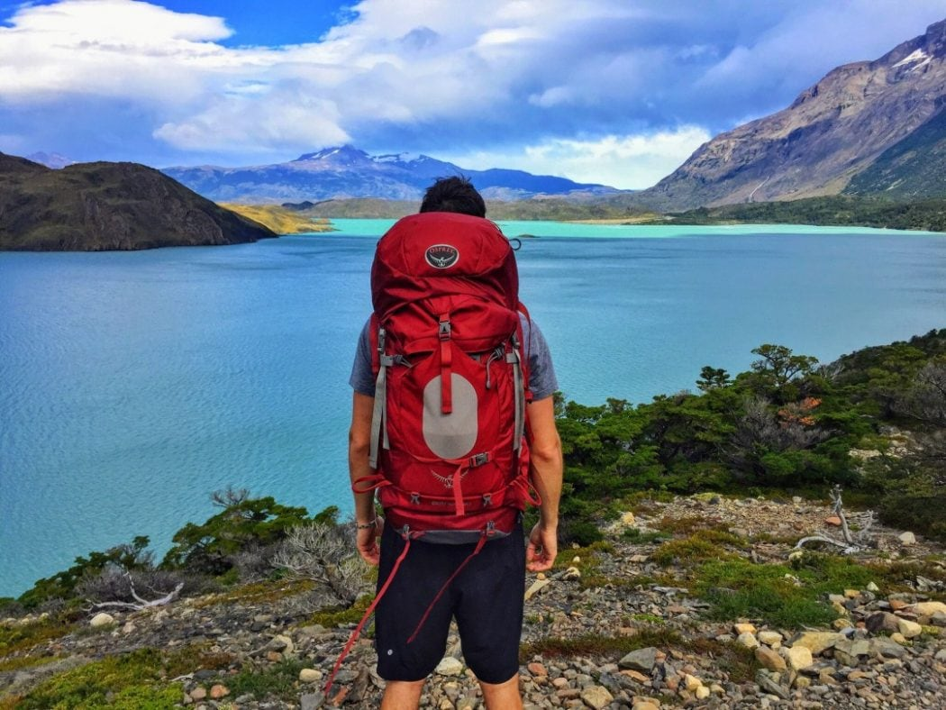 a man with his best travel backpack surveys a lake