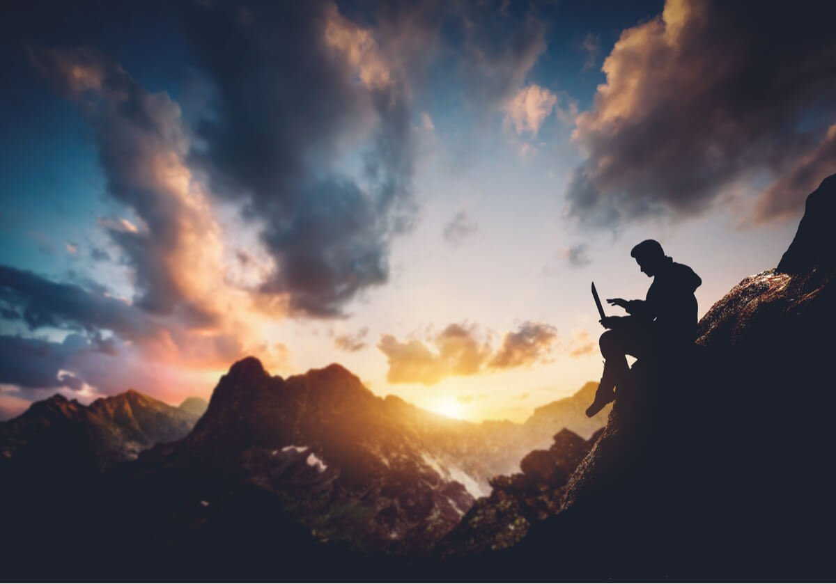 A digital nomad works on the road from a mountaintop