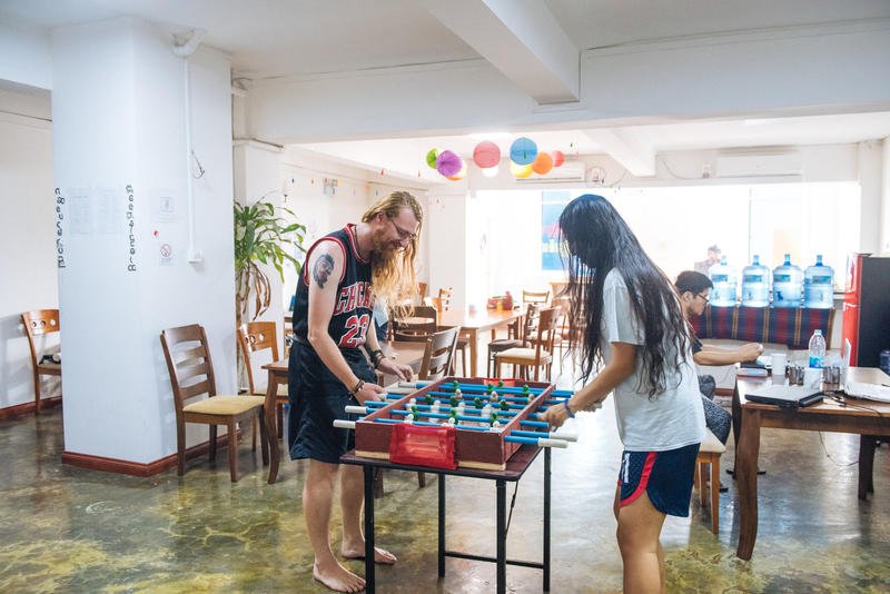 Backpackers playing foosball at a cheap hostel in Yangon