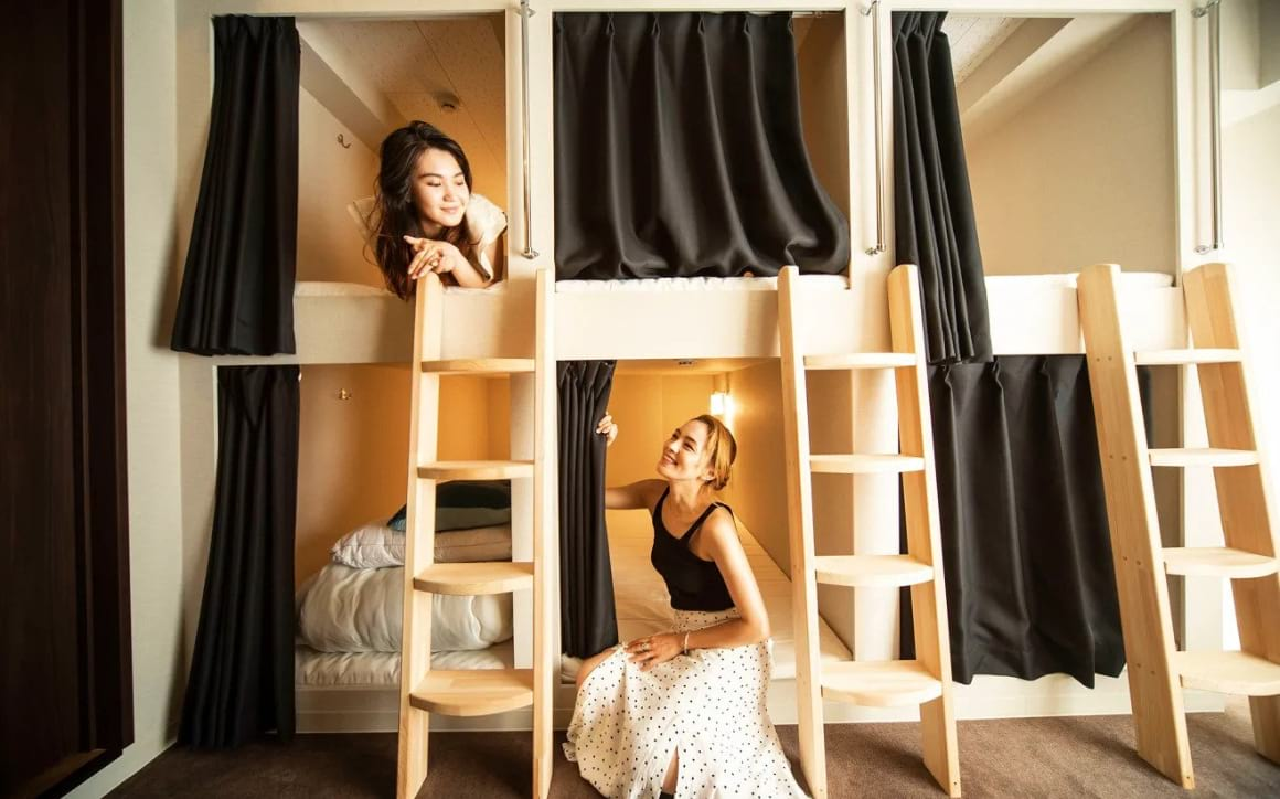 Two solo female travellers chatting in a hostel dorm in Japan