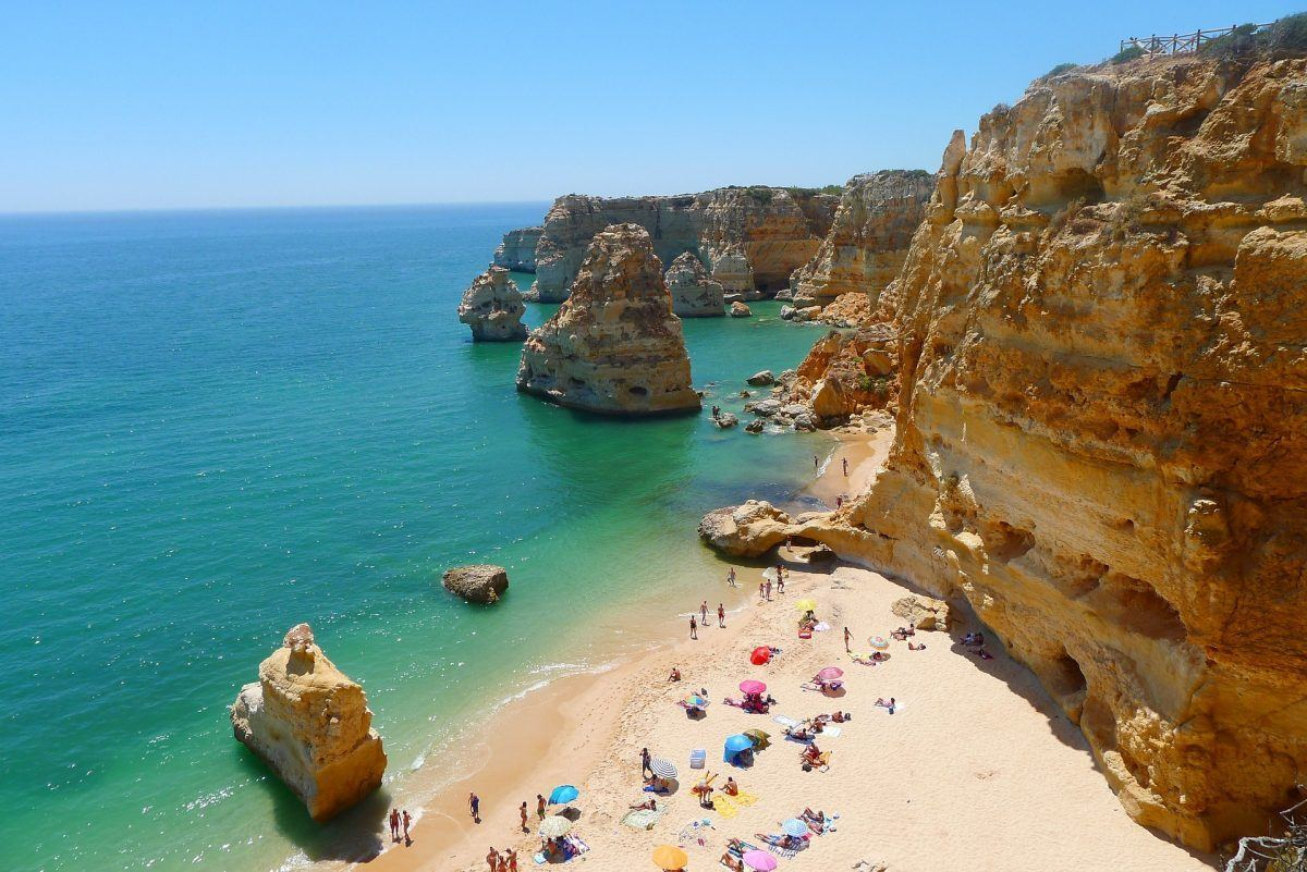 Sunny beach with sunbathers in algarve portugal