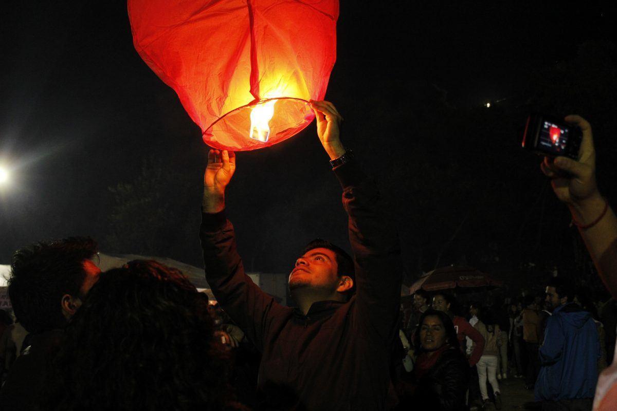 man releasing paper lantern at sao joao festiaval in porto portugal