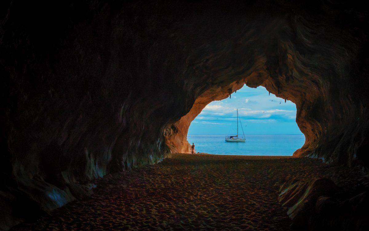 sailboat seen through the window of a grotto sardinia italy