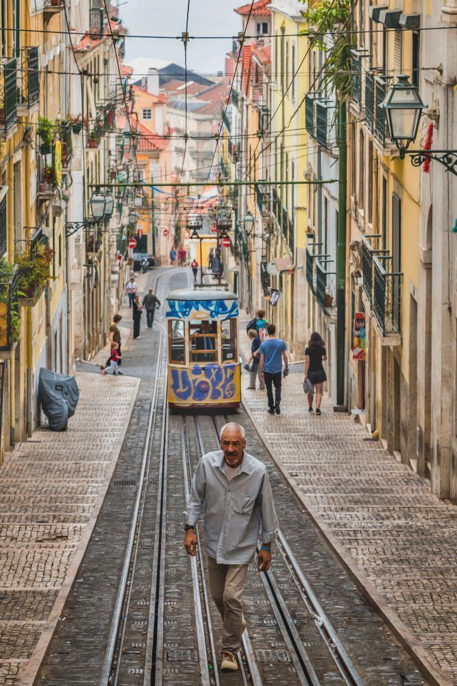 man in front of tram in lisbon portugal