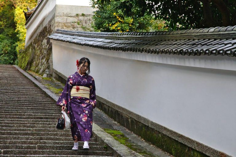 A woman wearing a traditional outfit in a neighborhood in Kyoto