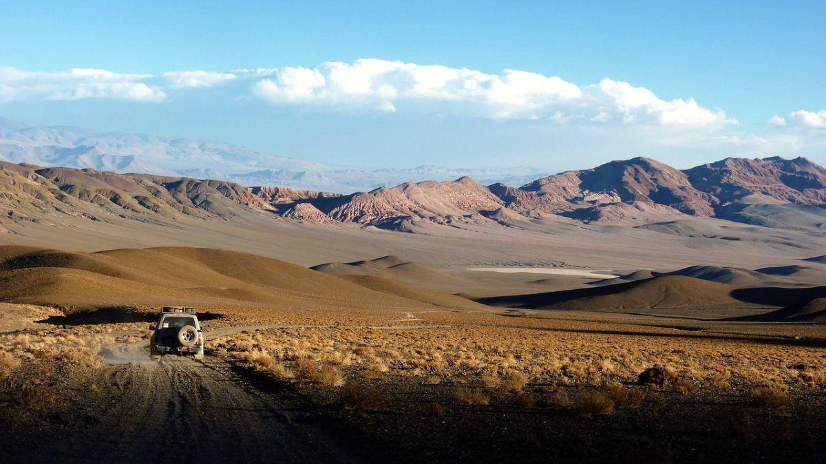 Car driving through empty desert landscape argentina