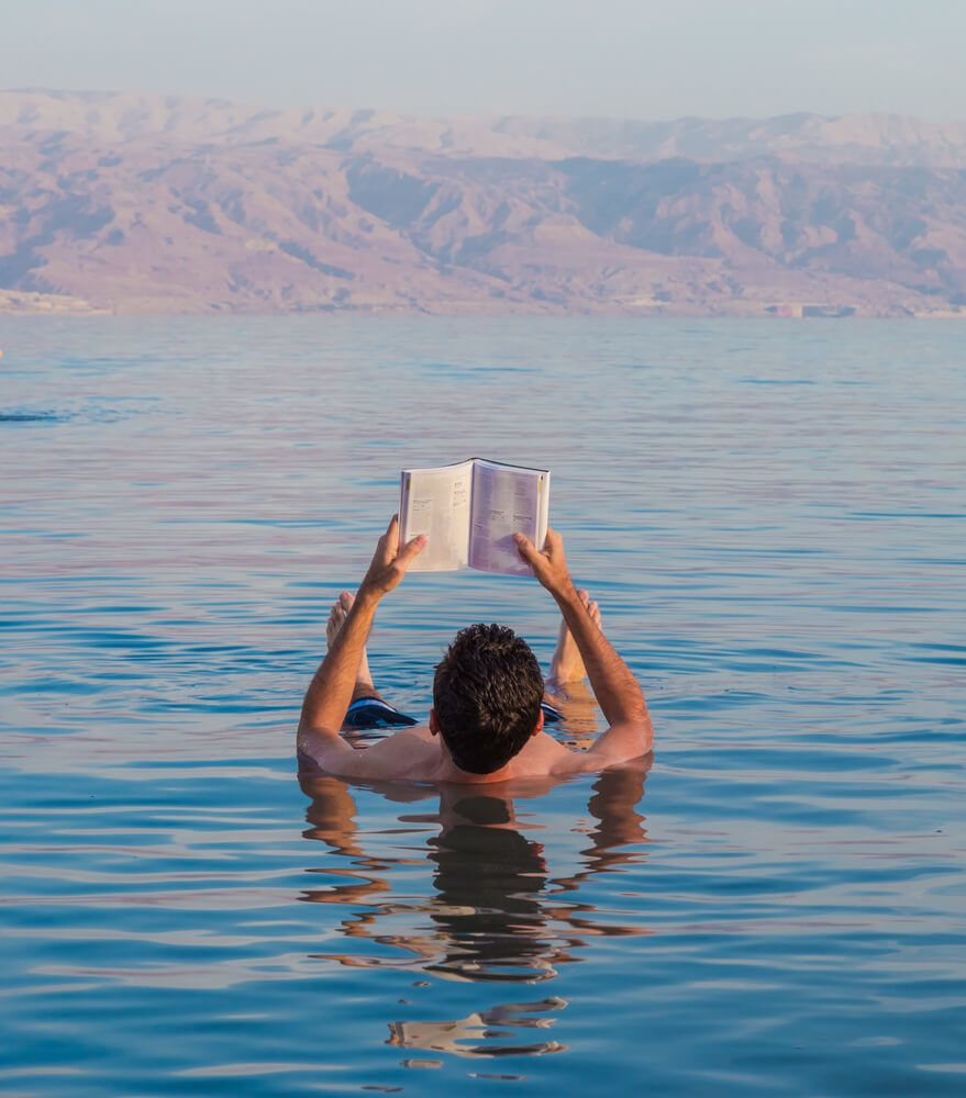 Man floating in the Dea Sea reading a book from the hostel
