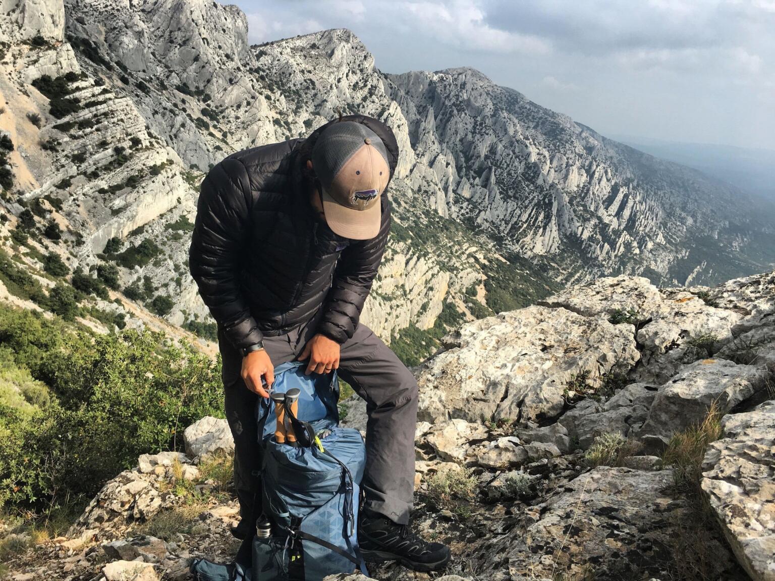 stowing trekking poles inside daypack