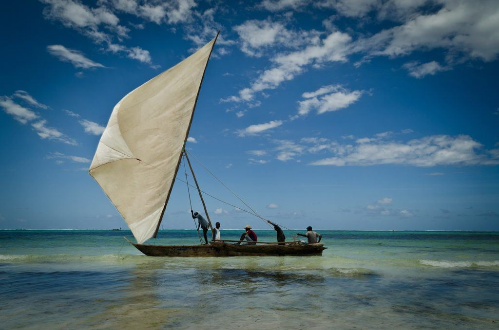 four men sailng a dhow (type of sailboat)