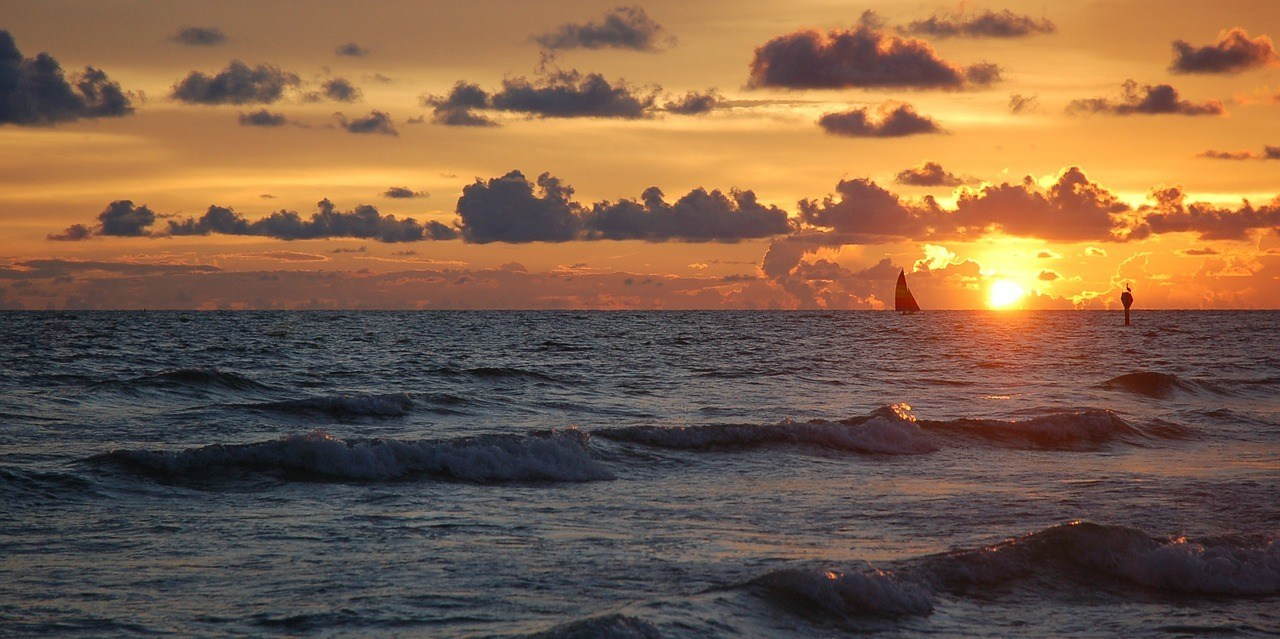 sunset florida with sailboat in water