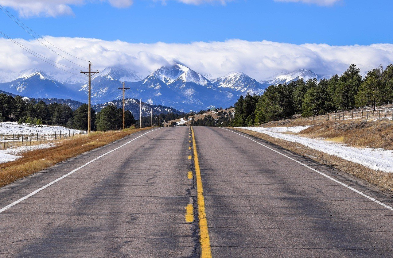 road in colorado leading to snowy mountains
