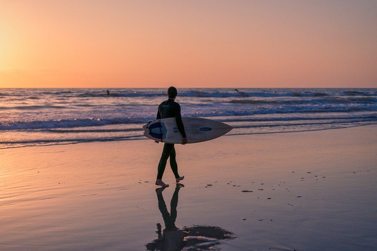 surfer walking beach at sunset in california
