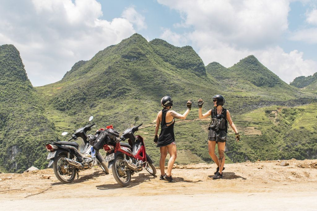 Two backpackers travelling by motorbike in Vietnam high-fiving on the Ha Giang Loop