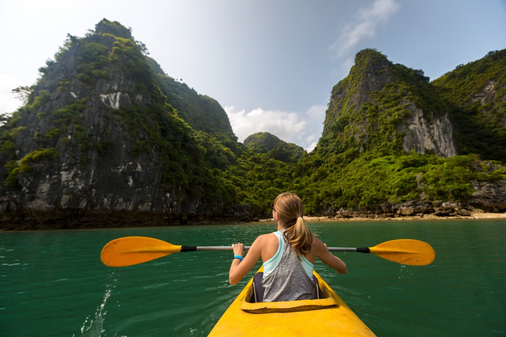 solo female traveller canoeing towards mountains in Vietnam