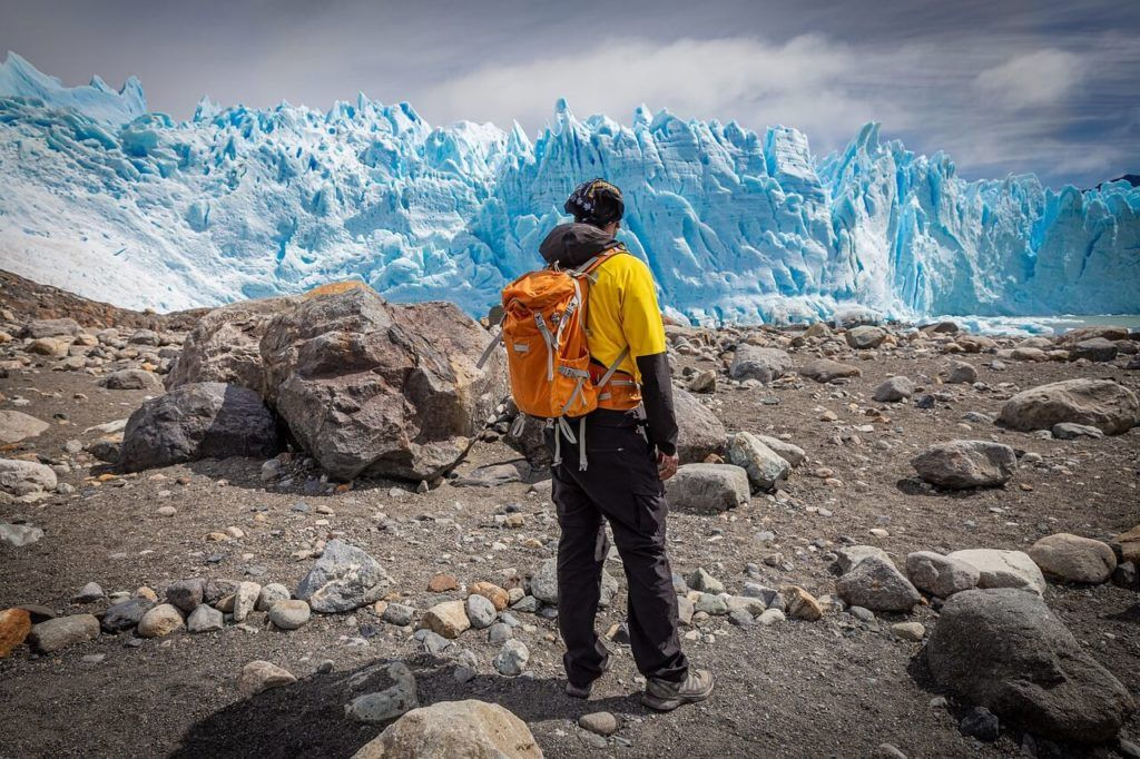 An iceberg in Argentina with a person wearing a yellow jacket in the foreground.