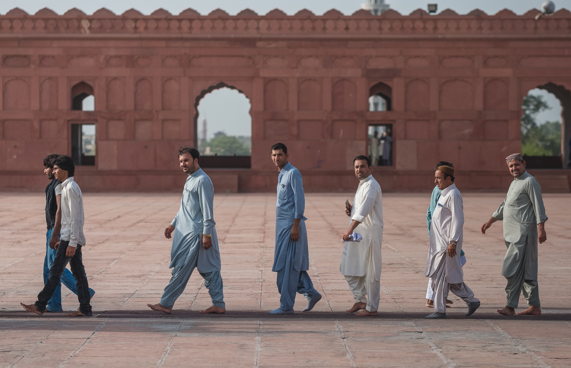 pakistani men walking at badshahi mosque pakistan