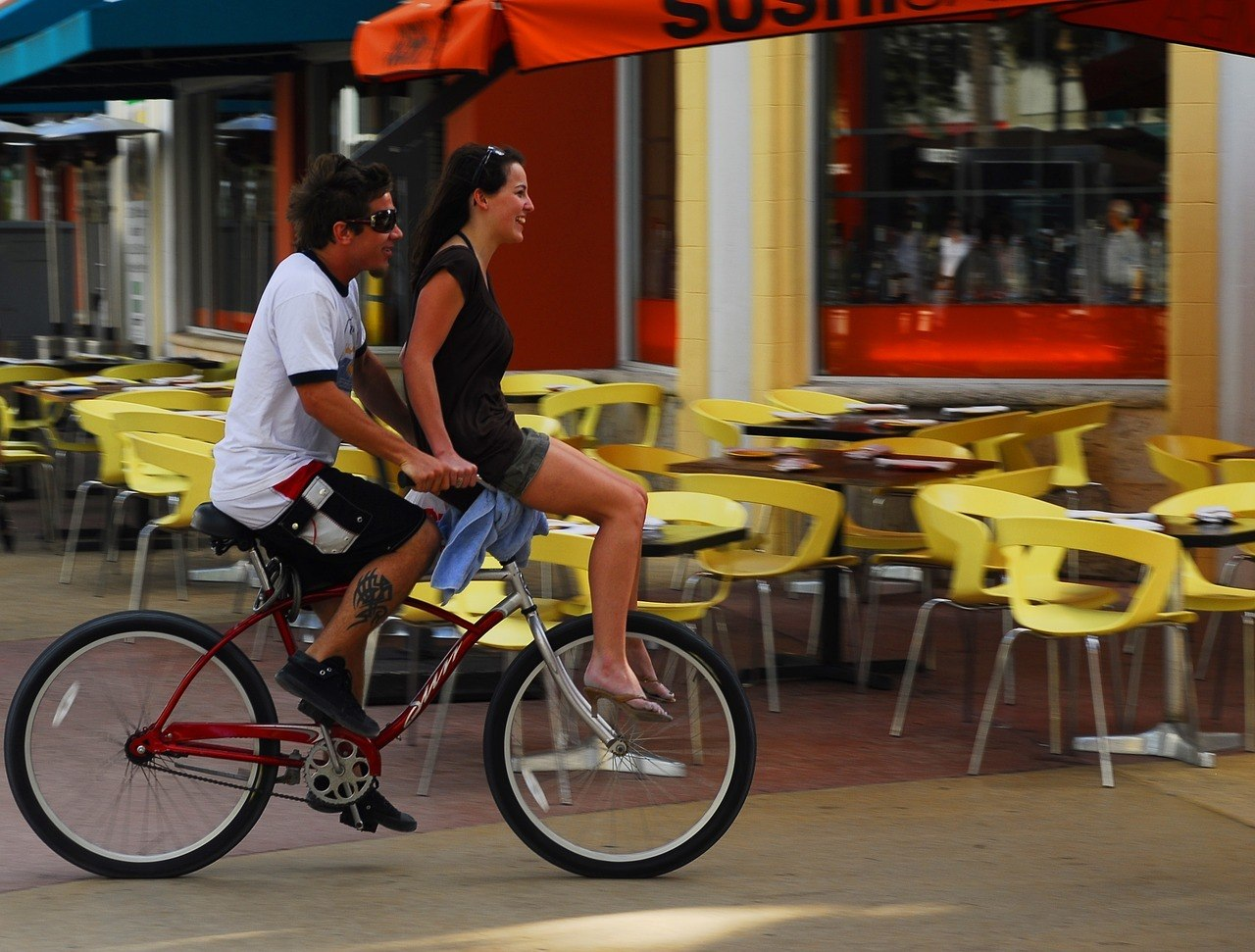 man and bike with girl miami travel guide