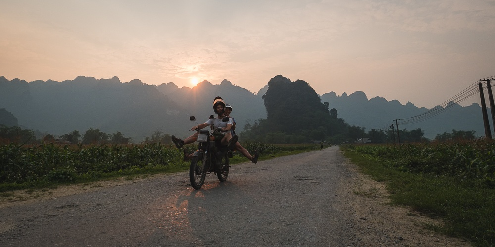 Two tourists travelling Vietnam by motorbike on a rural road