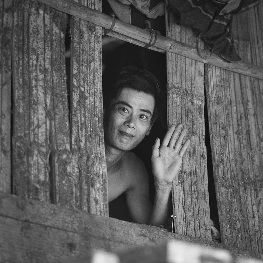 A friendly Vietnamese man waving from his house