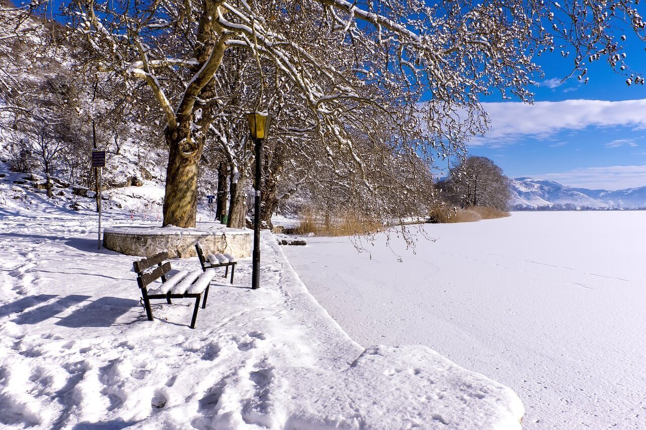A snowy bench in a park in winter in Greece
