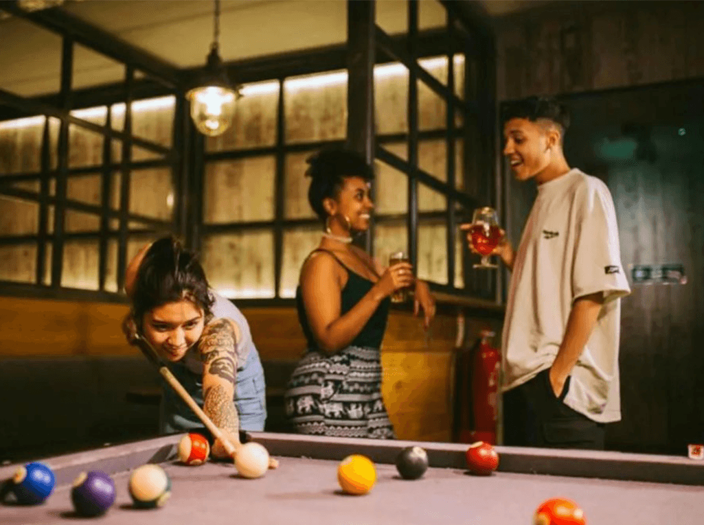 People staying at a hostel playing pool