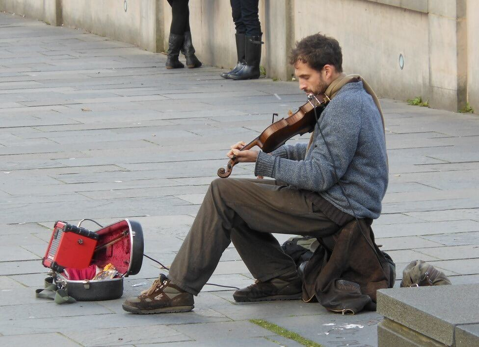 Solo man with a violin wondering where to busk