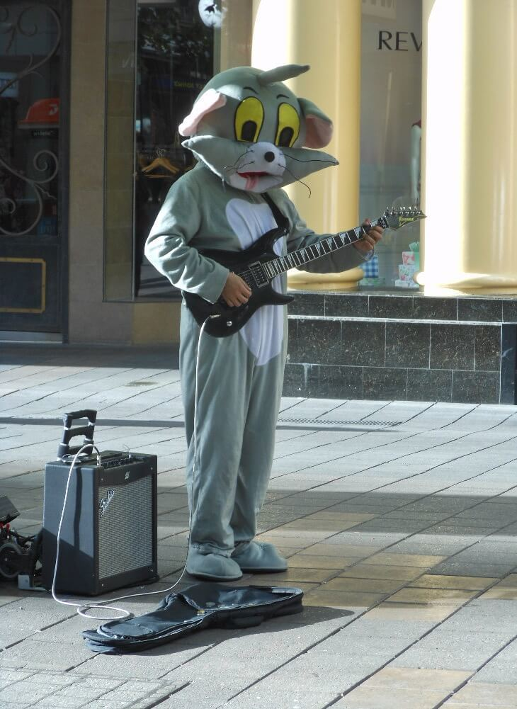 A backpacker busking in a cat costume