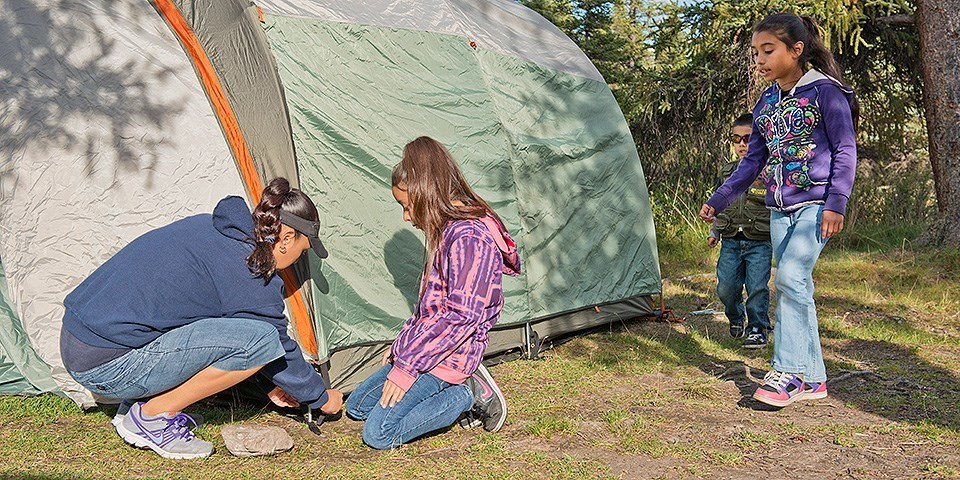Mum sets up the tent for kids
