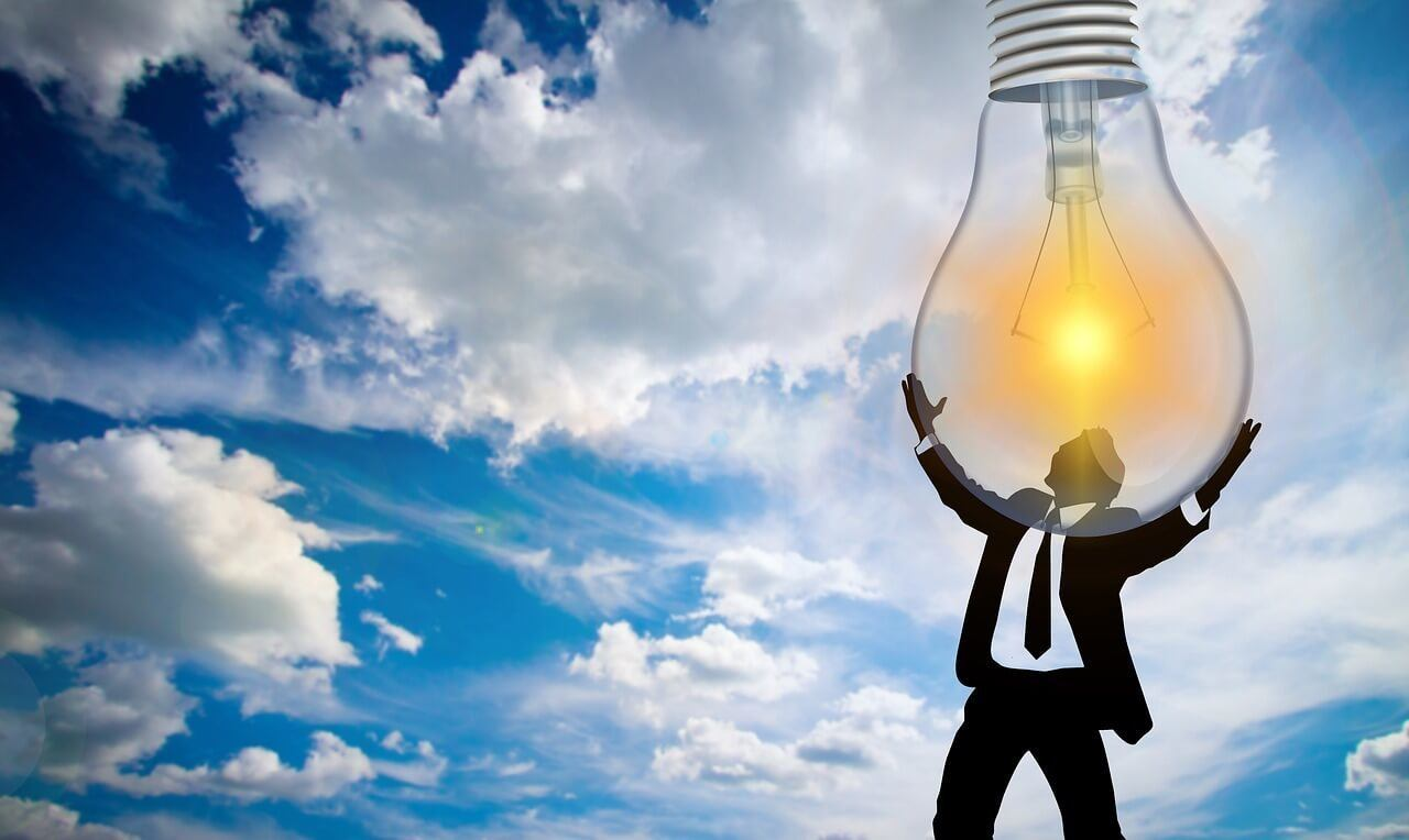 Man holding a lightbulb because his brain is overflowing with new vocabulary