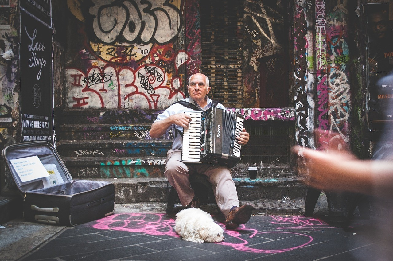Street performer busking for a living with his best friend