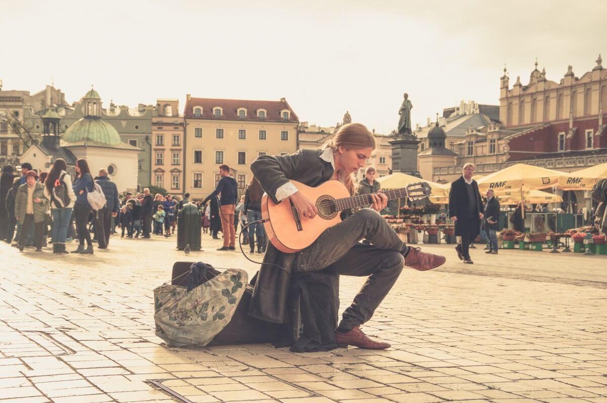 street performer in europe playing his traveling guitar