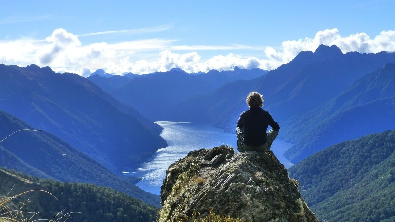 Man backpacking New Zealand sits on a point of interest in te Fiordlands