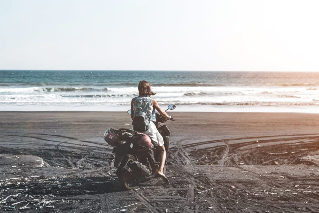 Young woman driving a scooter at the beach with black sand Bali Indonesia.