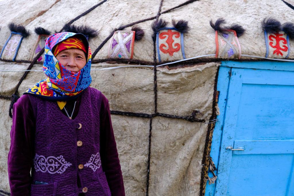 local woman outside yurt in kyrgyzstan