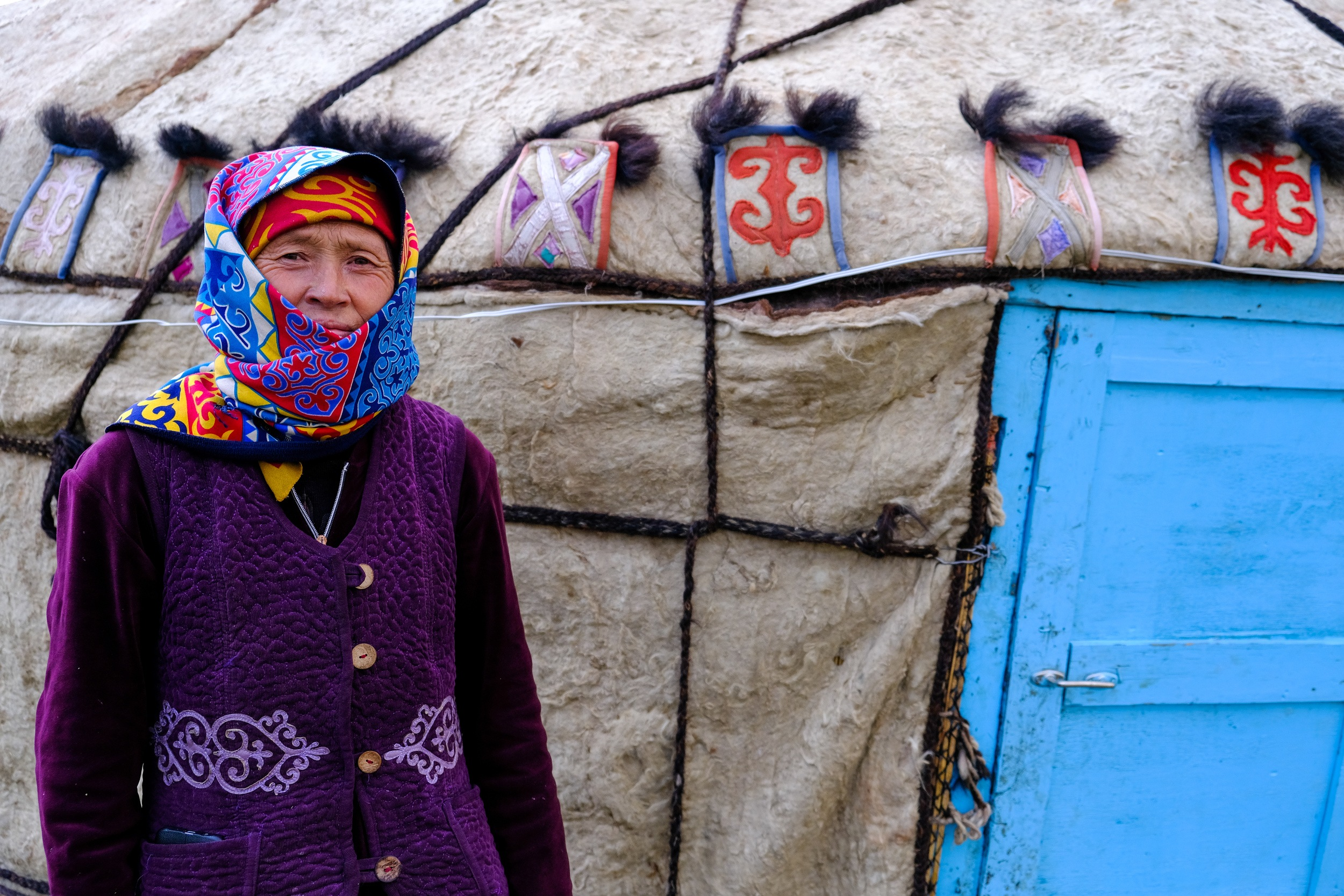 local woman outside yurt in kyrgyzstan