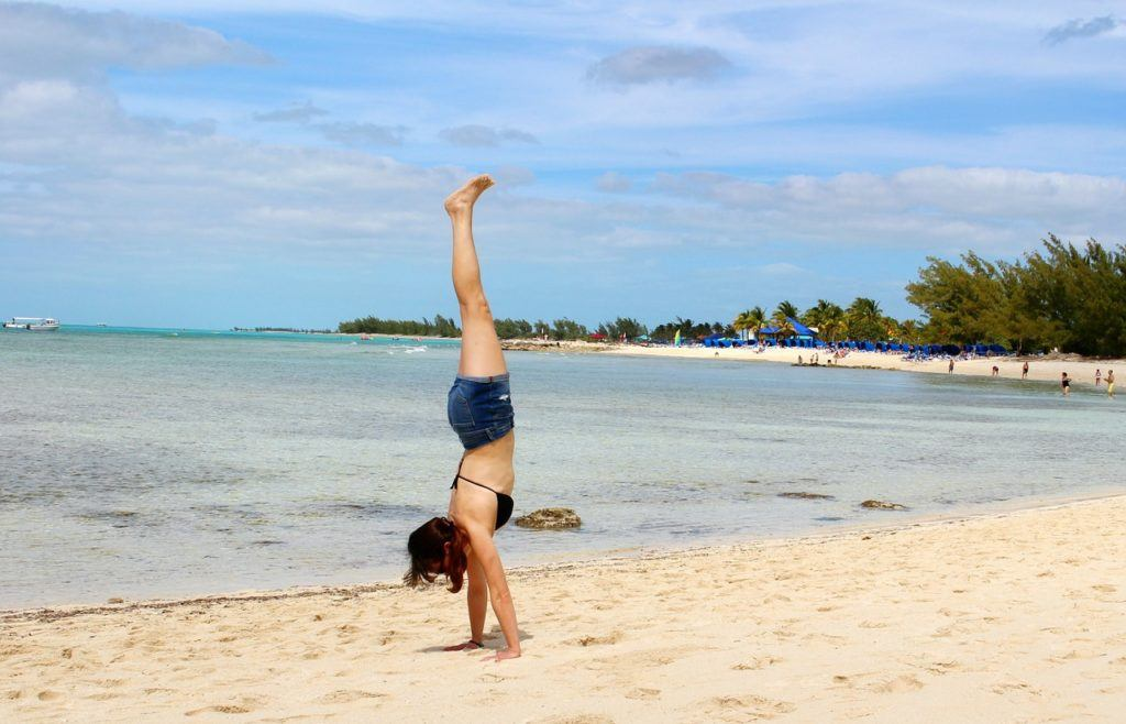 solo female traveller doing a handstand on a beach in Bahamas