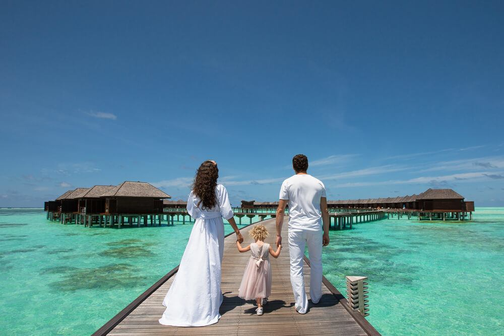 A family visiting a topical beach bungalow resort in Seychelles