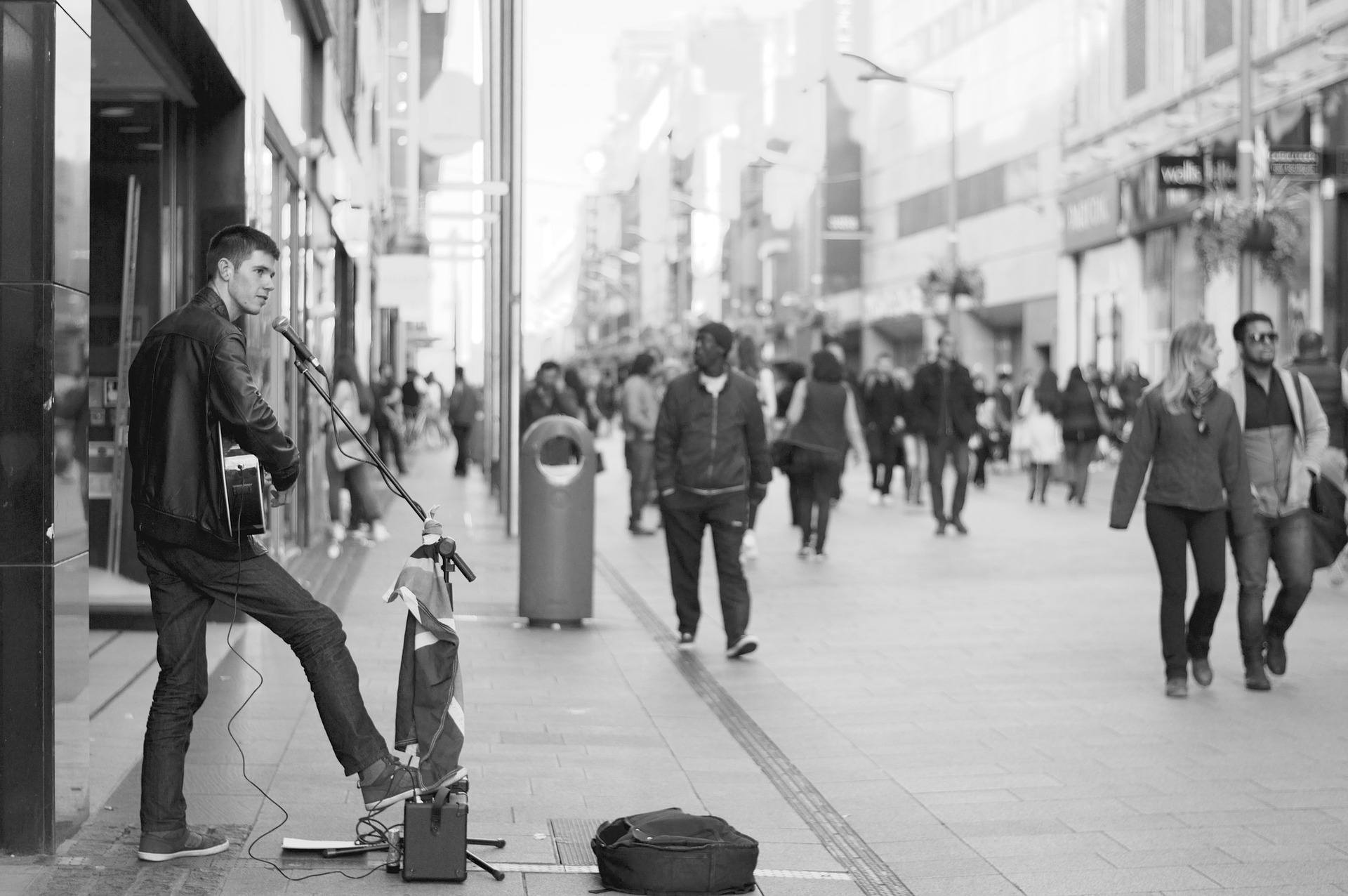 Black and white shot of man busking for money